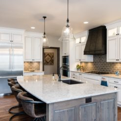 New Quay Cambria Quartz Kitchen Countertops with White and Gray Wood Cabinets, Wood Floors, and Bar Stools