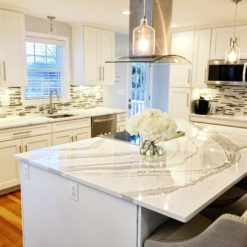 Brittanicca Warm Cambria Quartz Kitchen Countertops with White Cabinets, Stainless Steel, and Bar Stools