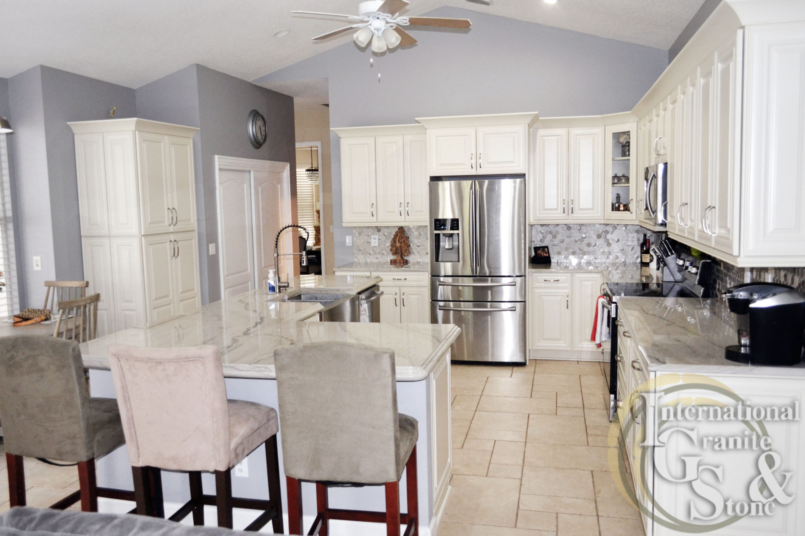 Calacatta Quartzite Kitchen with Bar Stool Chairs and White Cabinets