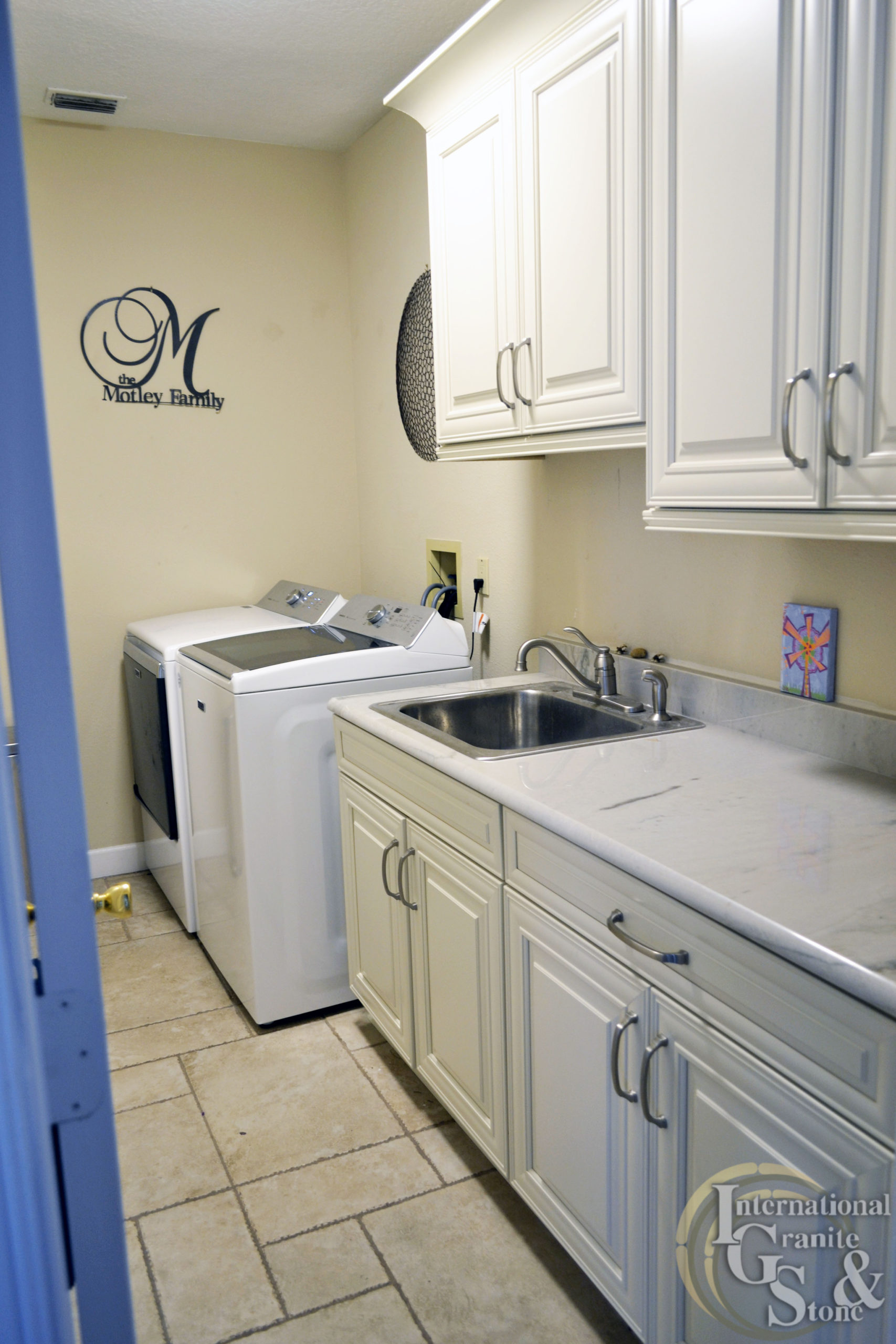 Laundry Room with Quartzite Counters and White Cabinets