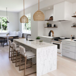 Brittanicca Block Cambria Quartz Kitchen Countertops with White Wood Cabinets, Wood Floors, and Bar Stools