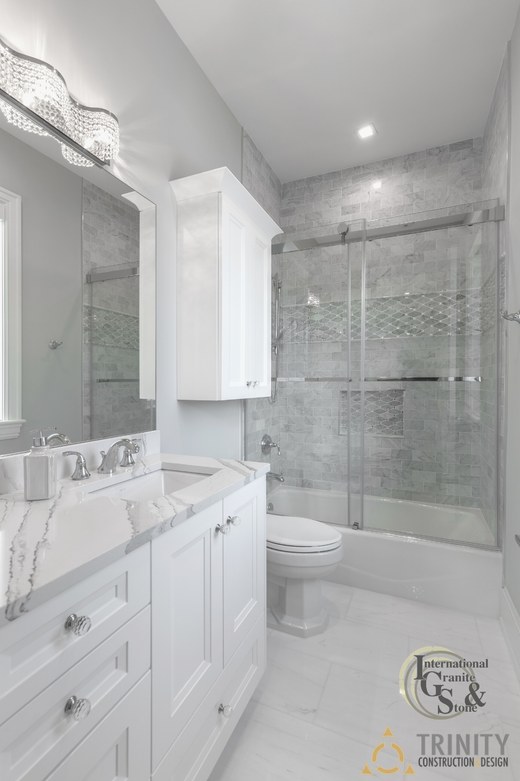 Light White Bathroom with Brittanicca Quartz Countertops and Gray Tile Backsplash Walls in Shower
